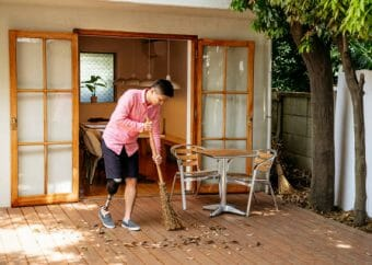 Male amputee in his 30s using broom to sweep decking in garden, differing ability, work, conquering adversity
